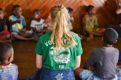A Childcare volunteer working with children in Fiji sits in a circle with children during a kindergarten lesson.